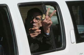 EgyptAir plane hijacking suspect Seif Eddin Mustafa flashes the victory sign as he leaves a court in a police car after a remand hearing as authorities investigate him on charges including hijacking, illegal possession of explosives and abduction in