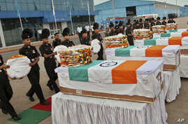 Indian soldiers pay tribute to their colleagues after their remains were returned at a wreath laying ceremony at the Palam Technical Airport in New Delhi, India, Aug. 7, 2013.