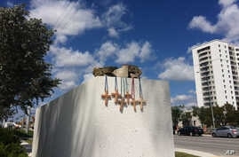 Six crosses are placed at a makeshift memorial on the Florida International University campus in Miami, March 17, 2018, near the scene of a pedestrian bridge collapse that killed at least six people on March 15.