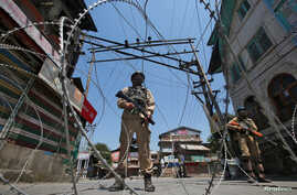 Indian policemen stand guard behind concertina wire during a strike called by separatists to mark the death anniversaries of chief cleric of Kashmir, Moulana Mohammad Farooq and Abdul Gani Lone, a Kashmiri separatist leader, in Srinagar, May 21, 2018