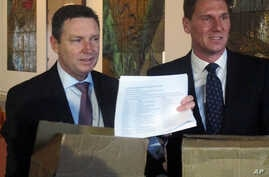 Australian Christian Lobby managing director Lyle Shelton, left, presents Australian Conservatives party leader Sen. Cory Bernardi, right, with 55,000 signatures on a petition at Parliament House in Canberra, Australia, Aug. 8, 2017.
