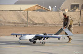 U.S. Marine pushes RQ-7B Shadow UAV drone following its landing at Camp Leatherneck, Afghanistan, Nov. 10, 2011.