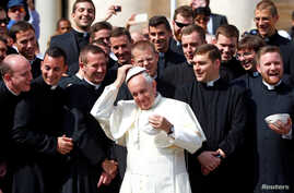 Pope Francis adjusts his skullcap as he poses with a group of priests during the weekly audience in Saint Peter's Square at the Vatican Sept. 28, 2016.