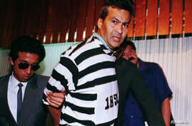 FILE - Drug trafficker Demetrio Chavez is shown to reporters in a striped uniform that previously had been reserved for guerrilla suspects, Jan. 27, 1994