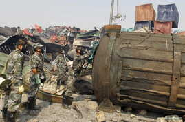 Soldiers of the People's Liberation Army's anti-chemical warfare corps, wearing gas masks, examine a container at the site of last week's explosions at Binhai new district in Tianjin, China, Aug. 16, 2015.