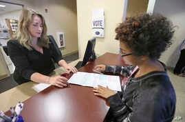 Sabine Kamagou, 19, right, gets help filling out a voter registration form from Cyndi Morrison, a worker in the Sacramento County registrar's office, in Sacramento, Calif., Oct. 22, 2018.