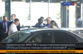 Image taken on Thursday, Aug. 1, 2013 and released by Russia24 TV channel, shows Russian lawyer Anatoly Kucherena, second right in the center, and National Security Agency leaker Edward Snowden, center back to a camera, Aug. 1, 2013.