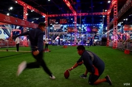 American football fans attempt a field goal at the NFL Experience, a fan festival in Houston, Texas leading up to the Super Bowl on Sunday, February 5th. (B. Allen/VOA)