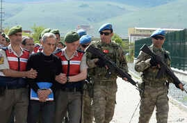Paramilitary police officers and commandos escort alleged instigators of last summer's failed military coup, including former Air Force commander Gen. Akin Ozturk, front, before their trial at a courthouse near Ankara, Turkey, May 22, 2017.