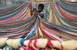 A boy separates starched sarees, a traditional Indian garment for women, left to dry on the roof of a cotton factory in the southern Indian city of Hyderabad, Nov. 30, 2012.