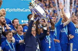Leicester team manager Claudio Ranieri and Wes Morgan lift the trophy as Leicester City celebrates becoming the English Premier League soccer champions at King Power Stadium in Leicester, England, May 7, 2016.