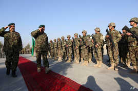 FILE - Gen. Sher Mohammad Karimi, chief of staff of the Afghan army, second left, salutes soldiers during a ceremony in Laghman province, east of Kabul, Afghanistan, Jan. 11, 2015.