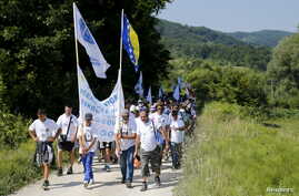 "People walk through a forest near the village of Nezuk Wednesday. Several thousand people started an 85-kilometer (53-mile) ""March for Peace"" from Nezuk to Srebrenica to retrace the route, in reverse, of Bosnian Muslims fleeing Serb forces in 1995."