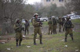 Israeli soldiers secure the scene after Palestinian teenager, Qusay Abo al-Rub, was shot and killed when he tried to stab a soldier in the village of Beita, south of the West Bank city of Nablus, Feb. 21, 2016.