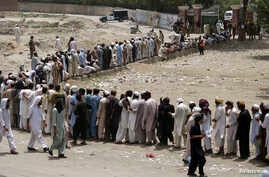 People, who fled the military offensive against Pakistani militants in North Waziristan, line up to receive food supply from the army in Bannu, in Pakistan's Khyber-Pakhtunkhwa province, June 25, 2014.