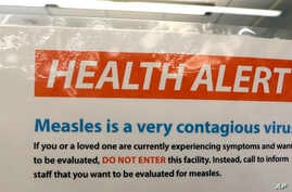 FILE - A notice for a health alert about measles is posted on the door of a medical facility in Seattle, Washington, Feb. 13, 2019.