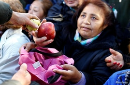 People receive free pears and apples during a protest staged by Argentine producers and farmers from the Patagonian provinces of Neuquen and Rio Negro for their losses in Buenos Aires, Argentina, Aug. 23, 2016.