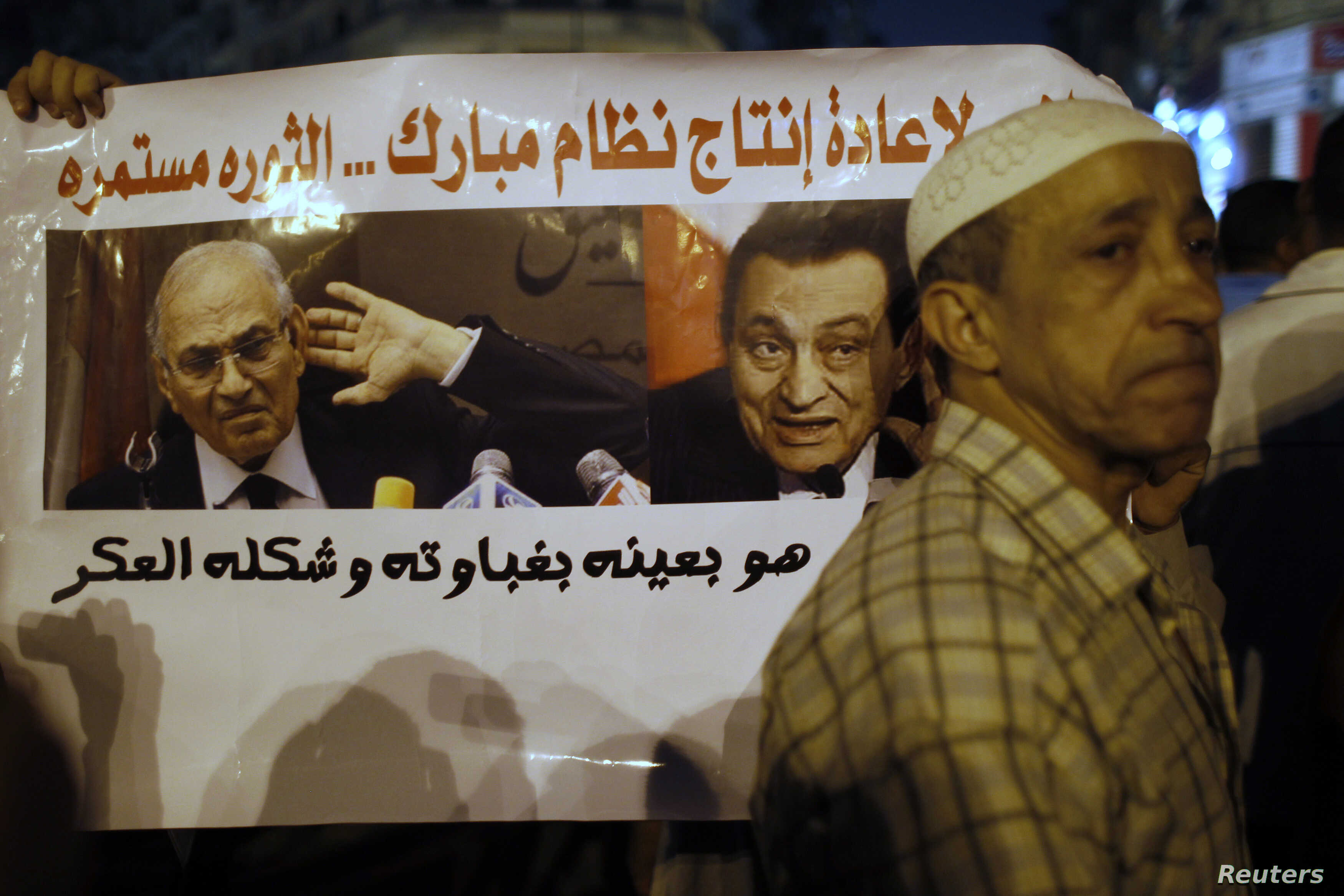 "With a sign that reads ""No to restoring the former Mubarak regime,"" in the background, protesters demonstrate against the results of the first round of Egypt's presidential elections at Tahrir Square in Cairo June 1, 2012."