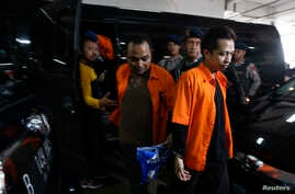 Indonesian policemen stand guard as Ahmad Junaedi, right, and Aprimul Henry alias Mulbin Arifin, center, who are accused of supporting Islamic State, arrive for their trial in Jakarta, Feb. 9, 2016.