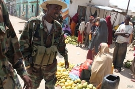 Women sell fruit at a market in Balad, Somalia on July 3, 2012, as soldiers stand guard. (VOA/M. Yusuf)
