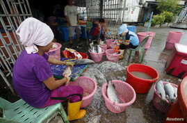 FILE - Migrant workers are seen during a police inspection at Songkhla, Thailand, Dec. 23, 2015. Thailand said this week seafood exports to the United States, Europe and Australia have not been hit by reports of slavery and forced labour by campaign