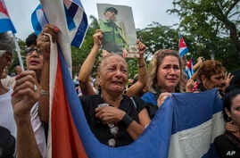 Women weep as the procession carrying the ashes of Cuba's leader Fidel Castro leaves the town of Santa Clara, Cuba, Dec. 1, 2016.