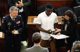 """Malian migrant Mamoudou """"Spider-Man"""" Gassama, center, is awarded Paris' Grand Vermeil medal by mayor Anne Hidalgo as the chief of the Paris' fire Brigade General Jean-Claude Gallet, left, applauds, June 4, 2018 at the city council room in Paris."""
