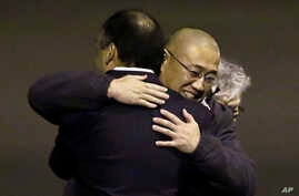 Kenneth Bae, center, who had been held in North Korea since 2012, is hugged after arriving at Joint Base Lewis-McChord, Washington, Nov. 8, 2014.