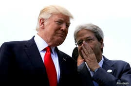 Italian Prime Minister Paolo Gentiloni speaks to U.S. President Donald Trump during a family photo at the G7 Summit expanded session in Taormina, Sicily, Italy, May 27, 2017.