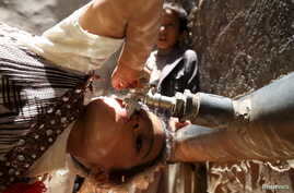A girl drinks water from a faucet amid an acute shortage of clean drinking water in Sanaa, Yemen, April 24, 2015.
