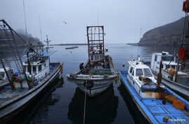 FILE - A fisherman sits on his boat in a small port on the island of Baengnyeong.