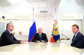 Russian President Vladimir Putin, center, watches the opening ceremony of natural gas pipeline from Russia to Crimea during a live video link from the Kremlin in Moscow, Dec. 27, 2016.
