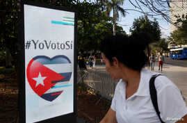 "A woman passes by a screen displaying images promoting the vote for ""yes"" for the constitutional referendum, in Havana, Cuba, Feb. 5, 2019."
