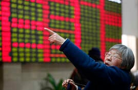 FILE - An investor gestures in front of the stock price monitor at a private securities company  in Shanghai, China.
