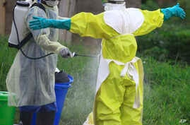In this photo taken Sept. 9, 2018, a health worker sprays disinfectant on his colleague after working at an Ebola treatment centre in Beni, Eastern Congo.