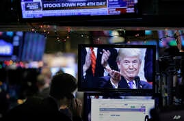 FILE- In this Dec. 24, 2018, file photo a picture of President Donald Trump is displayed on a computer on the floor of the New York Stock Exchange in New York. The Trump administration and China are facing growing pressure to blink in their six-month