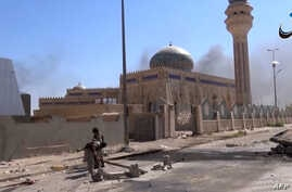 An image grab taken from a video uploaded on May 18, 2015 by Aamaq News Agency, a Youtube channel which posts videos from areas under the Islamic State (IS) group's control, allegedly shows IS fighters in a street of Ramadi.