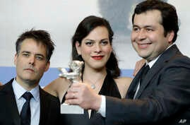 "From left, director Sebastian Lelio, actress Daniela Vega and writer Gonzalo Maza pose for the photographers with their Best Screenplay silver bear for the film ""A Fantastic Woman"" during the award winners press conference at the 2017 Berlin Internat"