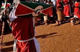 A traditional Burundian drummer dances with a shield and staff as he welcomoes a ruling party leader during a political rally at a sports field in Bujumbura, 11 May 2010
