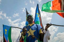 A man waves South Sudanese national flags during peace celebrations in the capital Juba, South Sudan, Oct. 31, 2018.