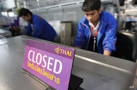 FILE - Airport staff inspect the ticketing counter at the Suvarnabhumi international airport in Bangkok.
