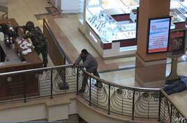 An image grab taken from AFP TV shows Kenyan troops taking position on September 21, 2013 inside the Westgate mall in Nairobi as a victim (R) lies on the ground.