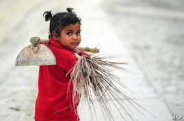 FILE - Young Indian child Laxmi carries a broom and hoe as she walks with her mother after working at the site of the annual traditional fair Magh Mela at Sangam, the confluence of the rivers Ganges and Yamuna, and the mythical Saraswati in Allahabad