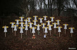 Twenty-seven wooden angel figures are seen placed in a wooded area beside a road near the Sandy Hook Elementary School for the victims of a school shooting in Newtown, Connecticut, December 16, 2012.