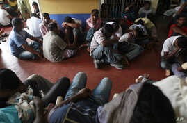 Would-be illegal asylum seekers from Sri Lanka are seen at a police station in Colombo, after being arrested near the shores of Negombo and the Galle Face for attempting to sail to Australia illegally by boat, May 28, 2012
