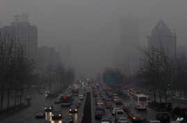 Endless lines of slow-moving cars emerge like apparitions and disappear into the gloom of the thick smog that has shrouded Beijing for weeks and reduced its skyline to blurry gray shapes, January 31, 2013.
