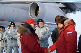 Russian President Vladimir Putin, center, shakes hands with Defense Minister Sergei Shoigu as he visits Franz Josef Land archipelago in the Arctic, Russia, March 29, 2017.