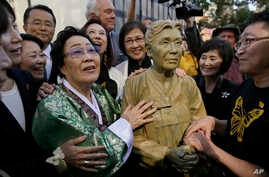 "Former World War II ""comfort woman"" Yongsoo Lee, 89, of South Korea, stands by a statue of Haksoon Kim while looking at the ""Comfort Women"" monument after it was unveiled, Sept. 22, 2017, in San Francisco."