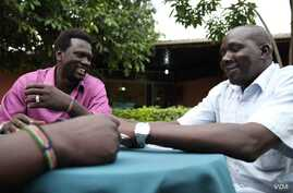 """Gatdet Thong (L) meets with other """"Cuban Jubans"""" wearing beaded bracelets with South Sudan's new flag colours, Juba, South Sudan, August 2012.  (H. McNeish/VOA)"""