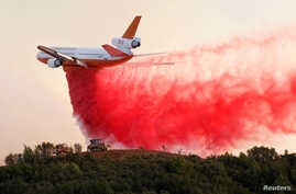 A DC-10 air tanker drops fire retardant along the crest of a hill to protect the two bulldozers below that were cutting fire lines at the River Fire (Mendocino Complex) near Lakeport, Calif.,  Aug. 2, 2018.